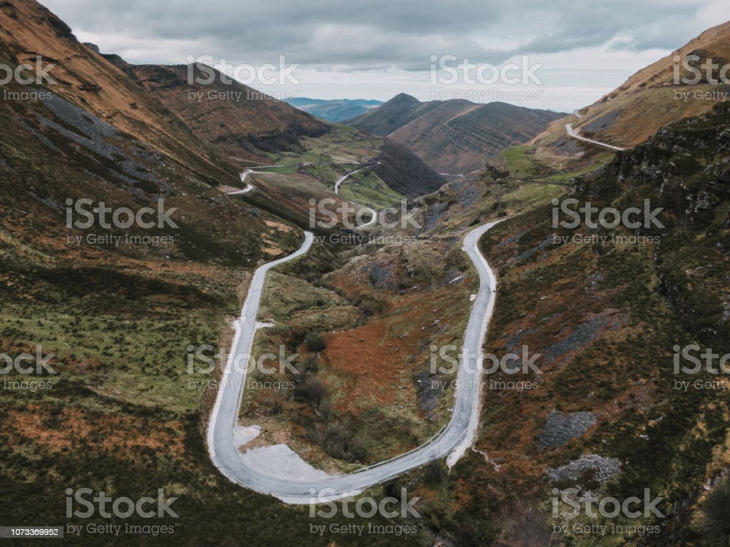 A mountain road with a hairpin curve as seen from above