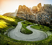 Beautiful mountain road with trees, forest and mountains in the backgrounds. Taken at state highway road in Passo Gardena, Sella mountain group of Dolomites mountain in Italy.