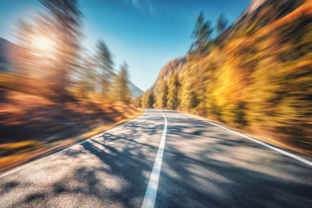 Mountain road in autumn forest at sunset with motion blur effect.  Asphalt road and blurred background with orange trees, blue sky with sun in fall. Fast driving. Beautiful highway. Transportation stock photo