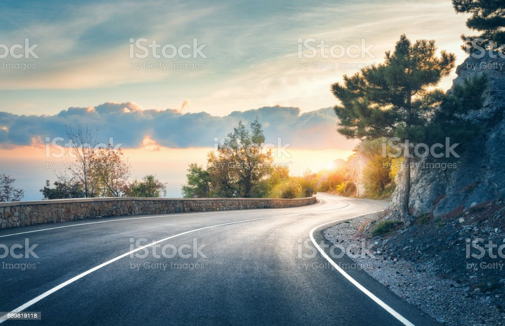 Mountain road. Landscape with rocks, sunny sky with clouds and beautiful asphalt road in the evening in summer. Vintage toning. Travel background. Highway in mountains. Transportation stock photo