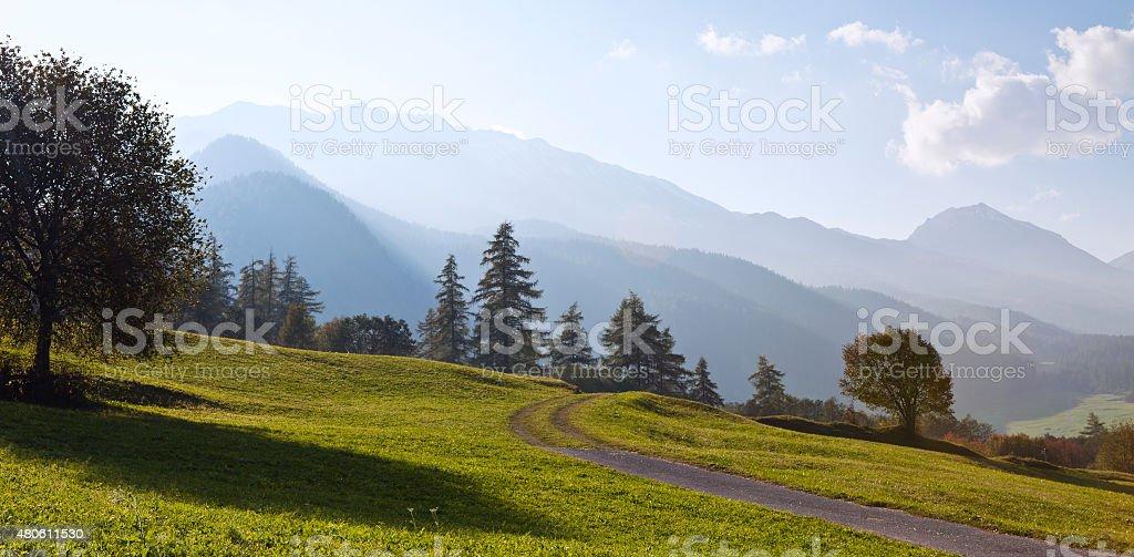 Mountain road through hazy valley, Val Müstair, Graubünden, Switzerland stock photo
