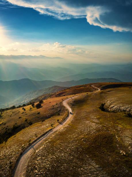 estrada de montanha com carro ao pôr do sol - estrada em terra batida - fotografias e filmes do acervo