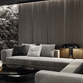 Modern matte black interior with mountain natural stone rock wall concept. Hotel lounge room interior.\nModern long corner sofa with black gloss coffee table and armchairs. \nBlack carpet and ceiling with down lighters. Light stone marble flooring. 3d rendering.