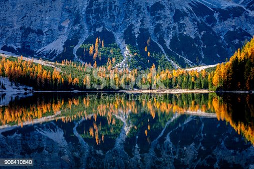 Mountain rocks and autumn forest reflected in water of Braies Lake, Dolomite Alps, Italy