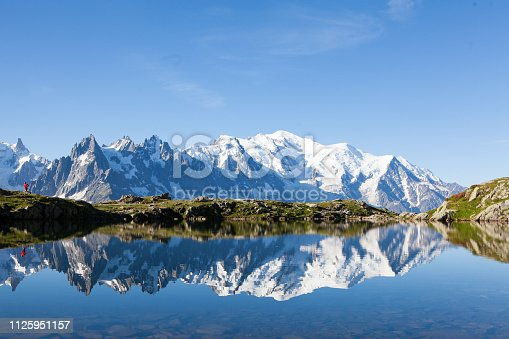 A runner explores the mountain trails near Chamonix in France, the Month Blanc is reflected in the lake