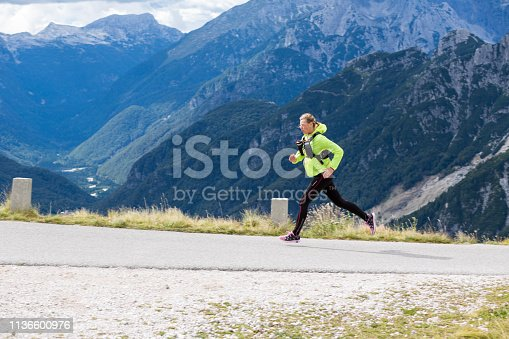 Man running in mountains. High pass road.