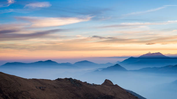Mountain silhouette and stunning sky with moon at sunset stock photo