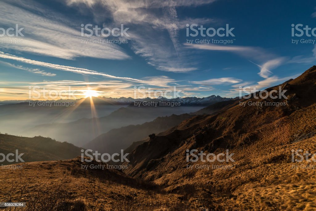 Colorful sunset behind majestic mountain peaks of the Italian Alps....