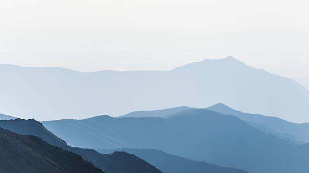 mountain silhouette at sunrise - telelens stockfoto's en -beelden
