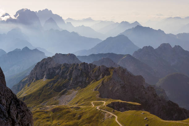 mountain silhouettes in the julian alps, slovenia, at sunset, in a warm late summer day, as seen comming down from mangart peak - slovenia foto e immagini stock