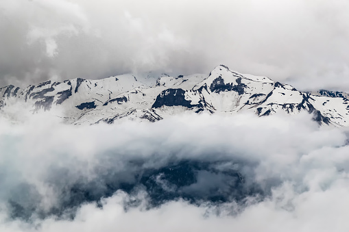 mountain snowy peaks covered with thick clouds, mysterious view of the mountain
