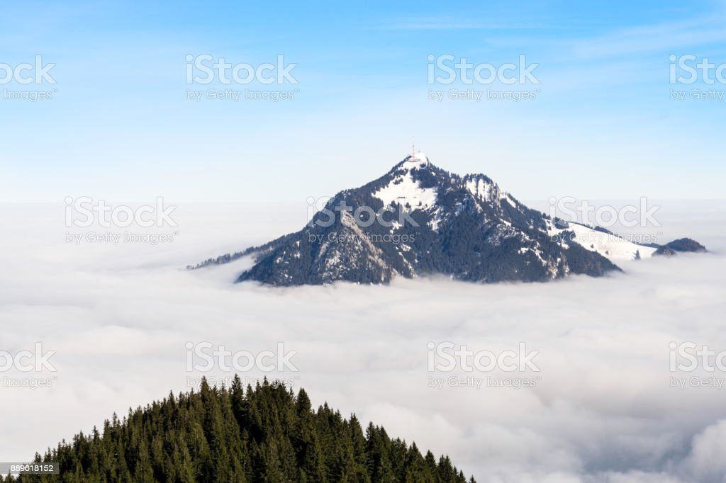 Mountain stick out of foggy cloud layer. Gruenten, Bavaria, Germany. Foresight and vision for business concept and ideas. stock photo