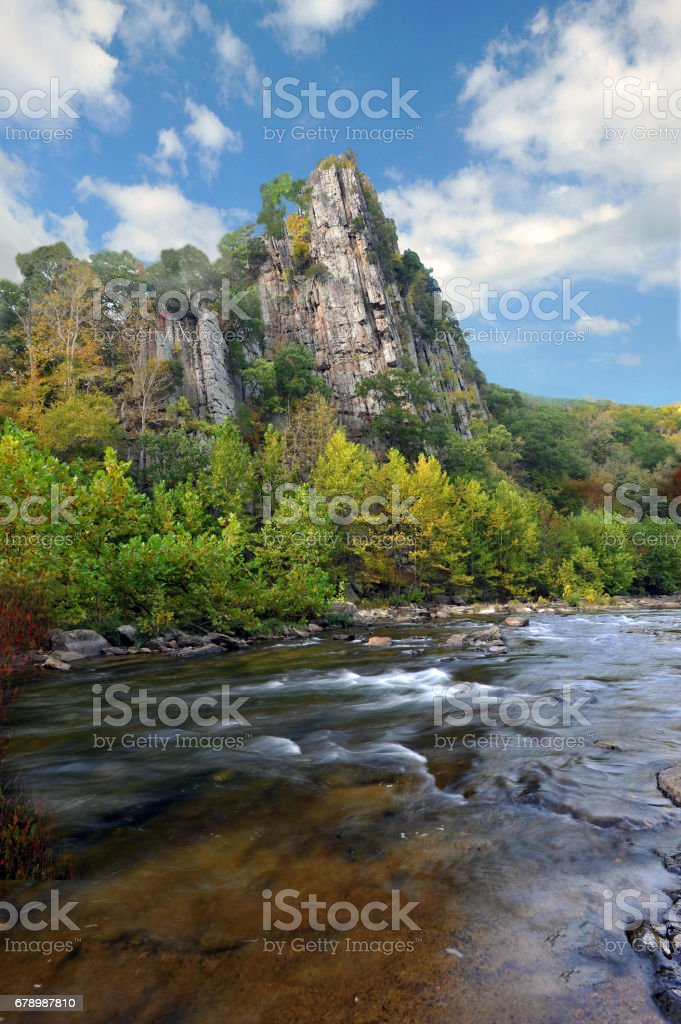 Mountain stream flowing in front of rock formation photo libre de droits