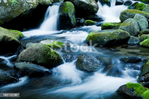 mountain stream flows through mossy rocks