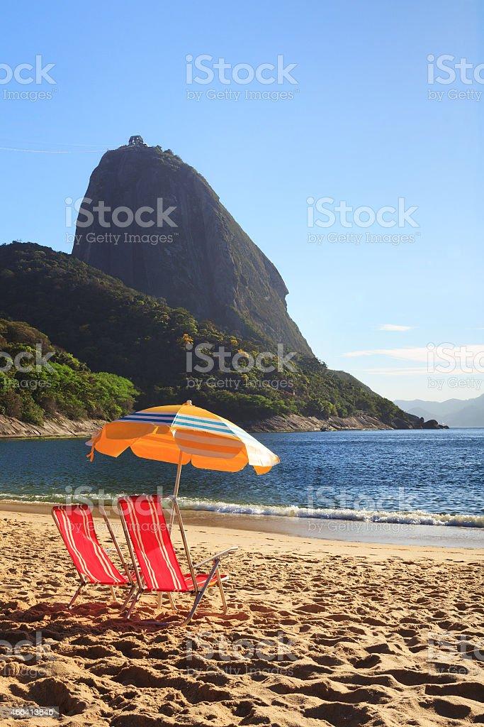 Mountain Sugarloaf sun umbrella and  chairs on  red beach (Praia stock photo