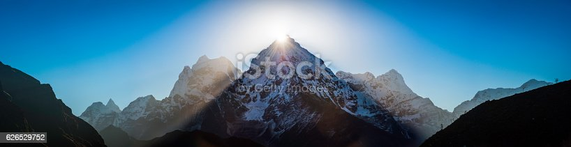 Bright rays of early morning sunlight bursting over the dramatic snowy peaks of Thamserku (6623m), Kangtega (6782m) and Kusum Kanguru (6367m) from the Thame valley deep in the Himalayan mountain wilderness of the Sagarmatha National Park, Solu Khumbu, Nepal.