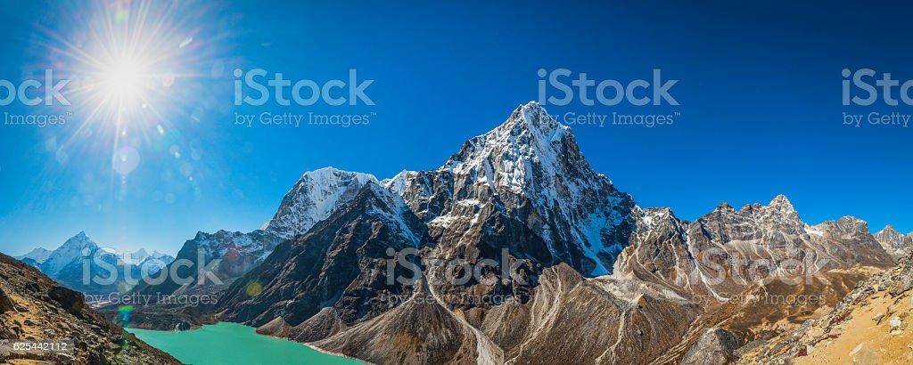 Mountain sunburst over dramatic Himalayan peaks panorama Khumbu Nepal stock photo