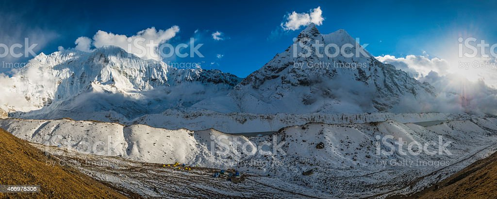 Mountain sunburst over dramatic snowy peaks panorama Himalaya basecamp Nepal stock photo