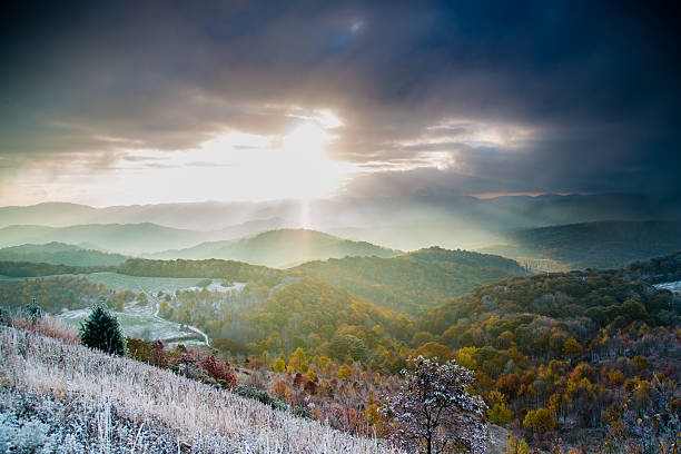 Mountain sunrise autumn with winter snow Mountain sunrise in the fall season with a winter snow dusting the landscape. Beautiful sun rays cast light across the mountain peaks and into the valley below. Taken in the blue ridge mountains of north carolina on the appalachian trail near max patch. appalachian mountains stock pictures, royalty-free photos & images
