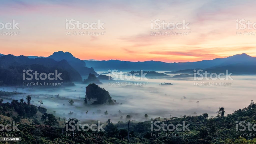 mountain sunrise with beautiful dramatic sky.morning fog in mountain valley before sunrise in winter season.Phu Langka mountain landscape with morning sea of fog in the background stock photo