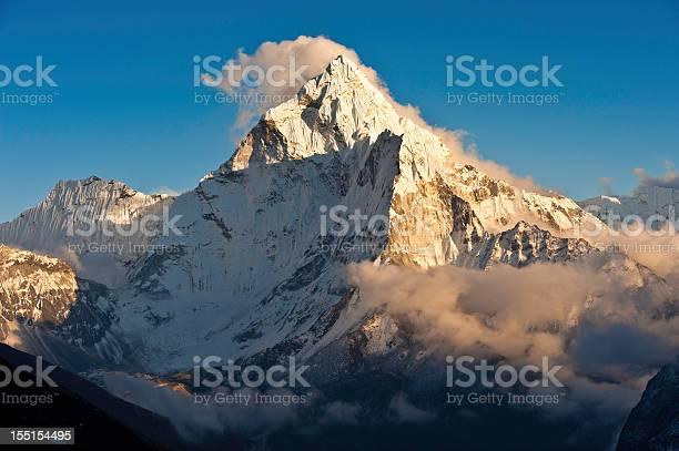 Photo of Mountain sunset golden light snowy peaks ridges