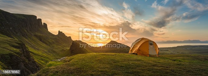Dome tent illuminated by the warm glow of sunrise as a golden cloudscape reveals the dramatic mountain pinnacles of this panoramic landscape. ProPhoto RGB profile for maximum color fidelity and gamut.
