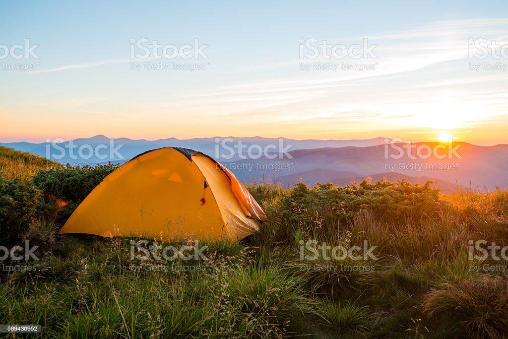 Yellow tent in the mountains, sunrise on the ridge, trekking, travel...