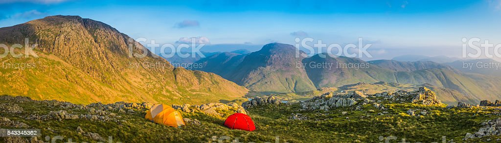 Mountain tents pitched high in wilderness camp panorama Lake District stock photo