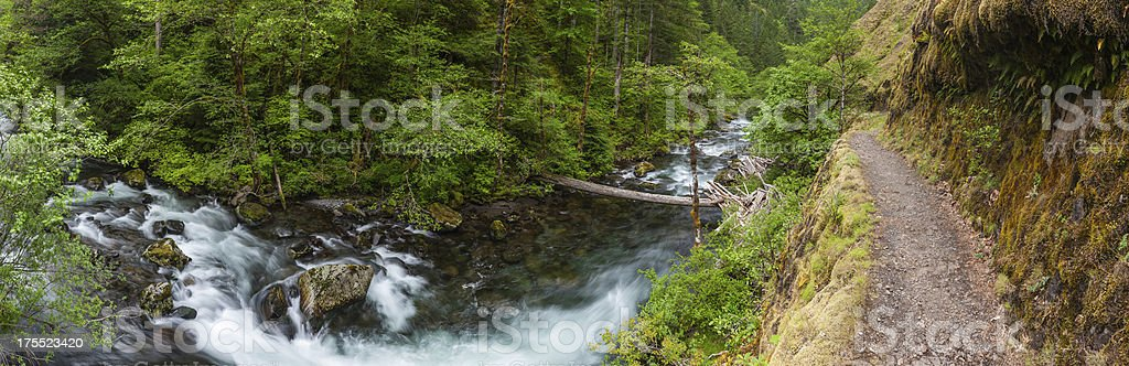 Mountain trail running along river ravine cascade panorama stock photo