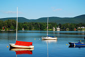 Pleasure craft rest on a cal and tranquil mountain lake in the Berkshire Mountains