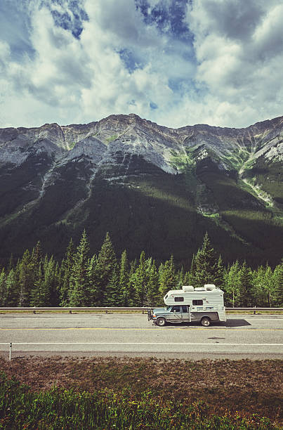 Mountain Vacation A pickup truck with camper top drives through the mountains near Kananaskis Alberta. kananaskis country stock pictures, royalty-free photos & images