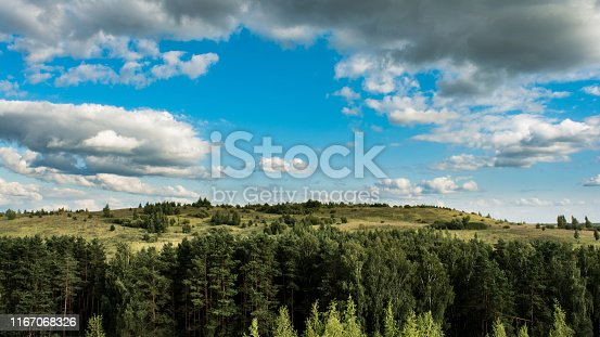 Mountain valley forest sky. Scenic top view on the valley, forest and mountains on the background of the sky with clouds on a sunny day