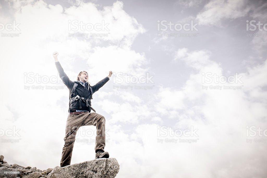Mountain Walking Man Celebrates on Cliff Edge stock photo