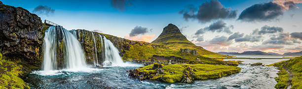 Mountain waterfalls below rocky peaks panorama at sunrise Kirkjufell Iceland - foto de acervo