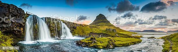 Photo of Mountain waterfalls below rocky peaks panorama at sunrise Kirkjufell Iceland