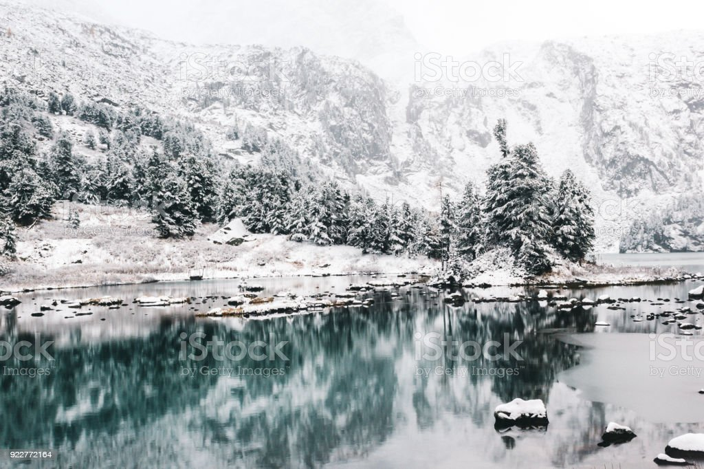 Mountain winter lake with the reflection of rocks in the water surface. High-altitude beautiful lake with clear mirror water. Purity beauty of the Altai nature. stock photo