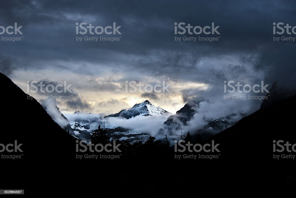 Mountain with Clouds, Fog, Trees, Mist at Sunset stock photo