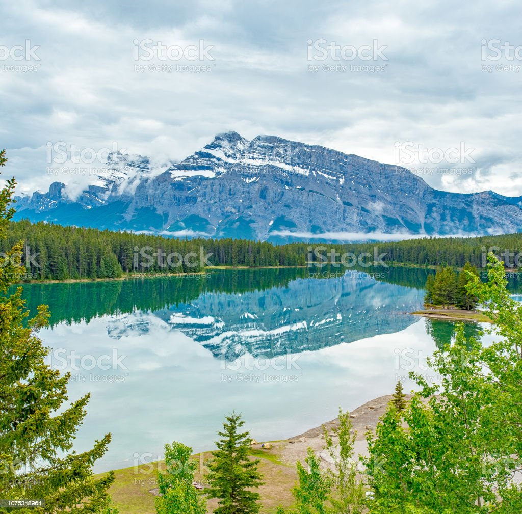 mountain with mirror image reflected in alpine lake surrounded by douglas fir trees on a cloudy morning in spring time. stock photo