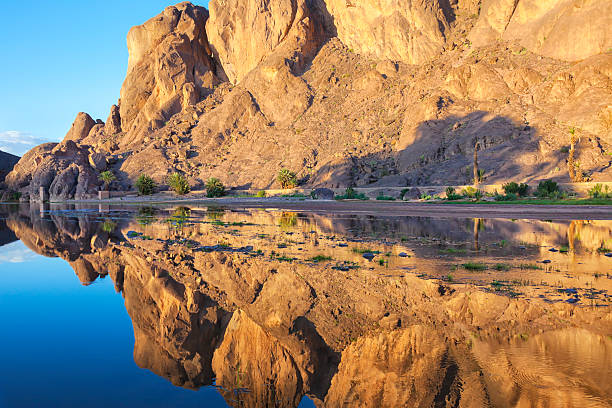 Mountain with reflections in a river, Fint Oasis. stock photo