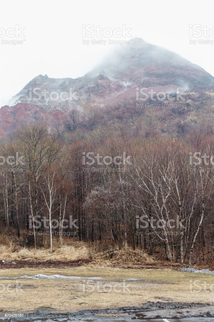 Mountain with snow and fog on the top and trees below at carpark of Noboribetsu Bear Park in Hokkaido, Japan. stock photo