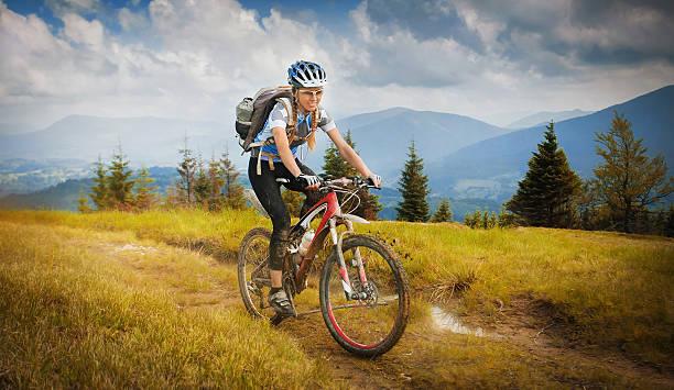 mountain-bike Woman mountain-bike riding on ridge with Carpathian Mountains mountain biking stock pictures, royalty-free photos & images