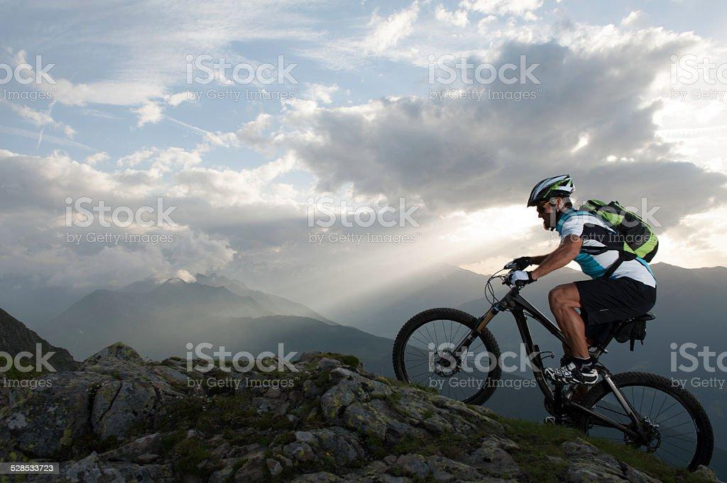 mountainbike uphill on mountain ridge stock photo