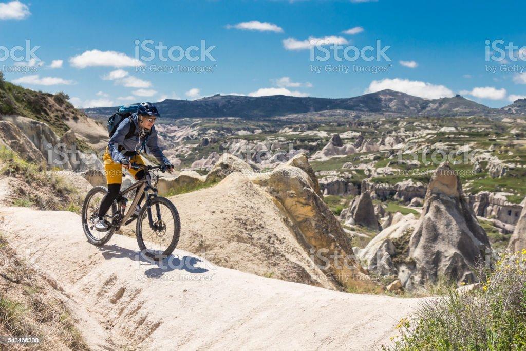 Mountainbiker balancing on white tuff formation, Cappadocia, Turkey stock photo