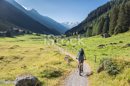 A female mountain biker is riding on a footpath in the morning into scenic Dischma Valley nearby Davos which is a large alpine city in the canton of Graubünden. The region is famous for lots of outdoor sports activities in summer as well as in wintertime. Canon EOS 5D Mark IV, 1/500, f/4, 32 mm.