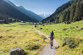 A female mountain biker is riding on a footpath in the morning into scenic Dischma Valley nearby Davos which is a large alpine city in the canton of Graubünden. The region is famous for lots of outdoor sports activities in summer as well as in wintertime.\nCanon EOS 5D Mark IV, 1/500, f/4, 32 mm.