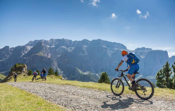 Ein Mountainbiker schließt andere Mountainbiker auf eine Fahrt in den Dolomiten, Italien – Foto