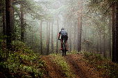 Revda, Russia - July 31, 2016: male athlete mountainbiker rides a bicycle along a forest trail. in forest mist, mysterious view during Regional competitions on cross-country bike