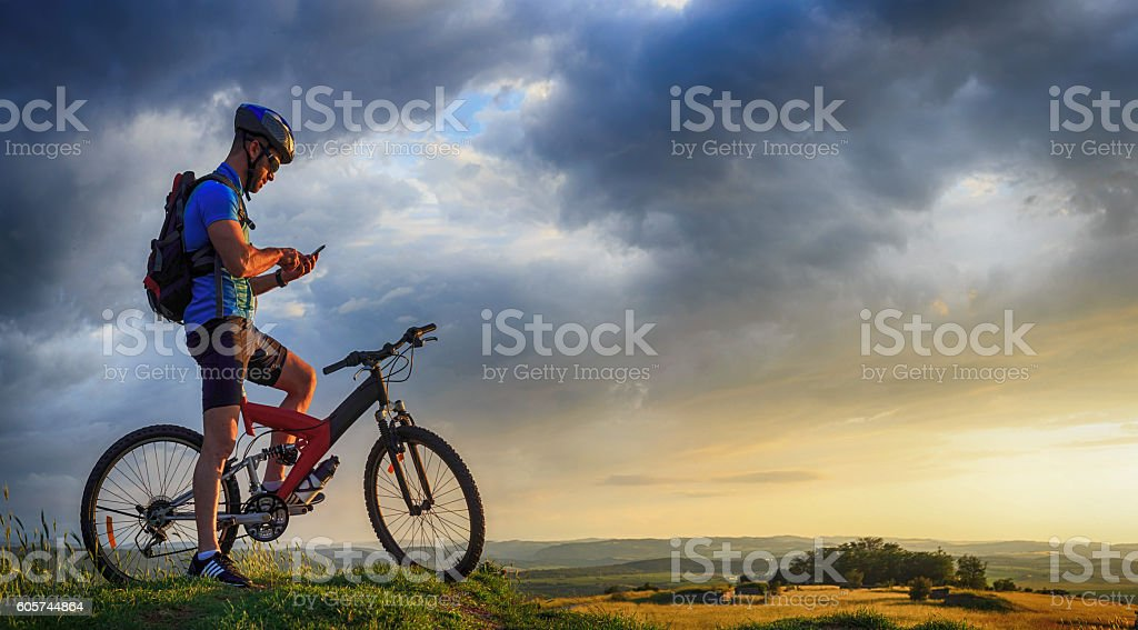 Mountainbiker using mobile phone on top of the mountain stock photo