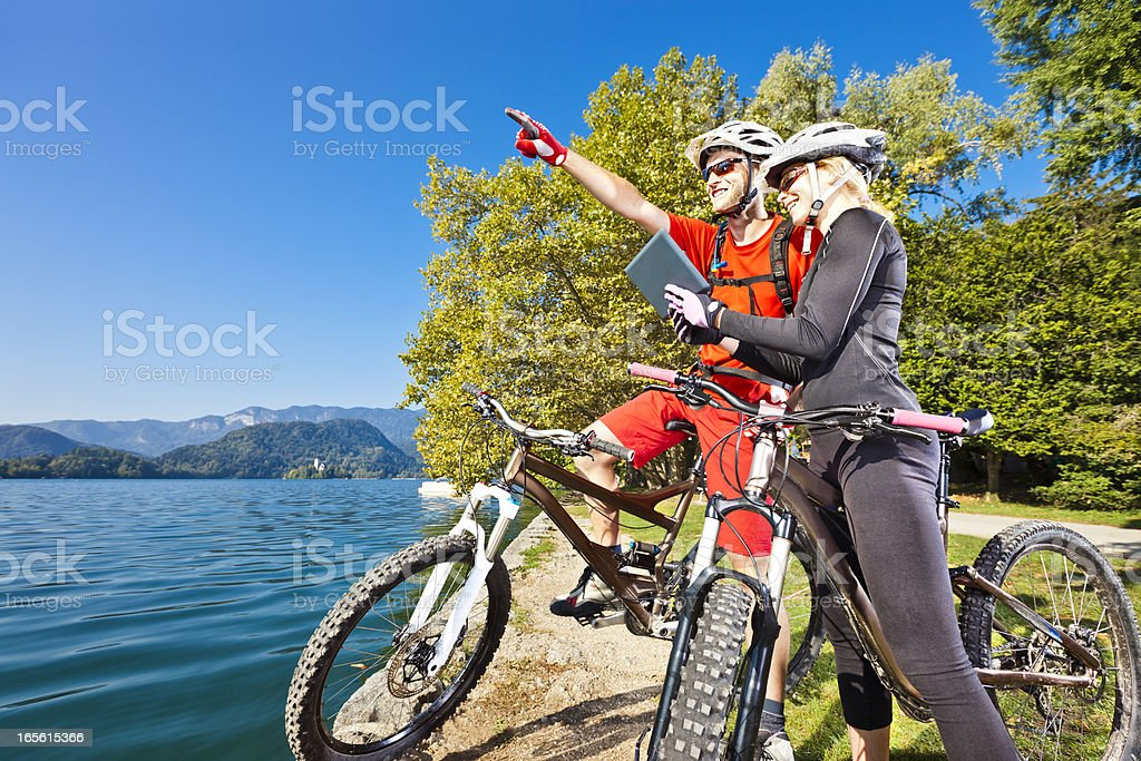 Mountainbikers navigating with digital tablet royalty-free stock photo