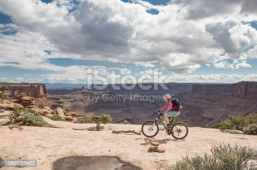 A female mountainbiker is riding close to the rim at Dead Horse Point State Park which is a state park of Utah in the United States, featuring a dramatic overlook of the Colorado River and Canyonlands National Park. The park covers 5,362 acres (2,170 ha) of high desert at an altitude of 5,900 feet (1,800 m). Canon EOS 5D Mark IV, 1/800, f/7,1 , 24 mm.
